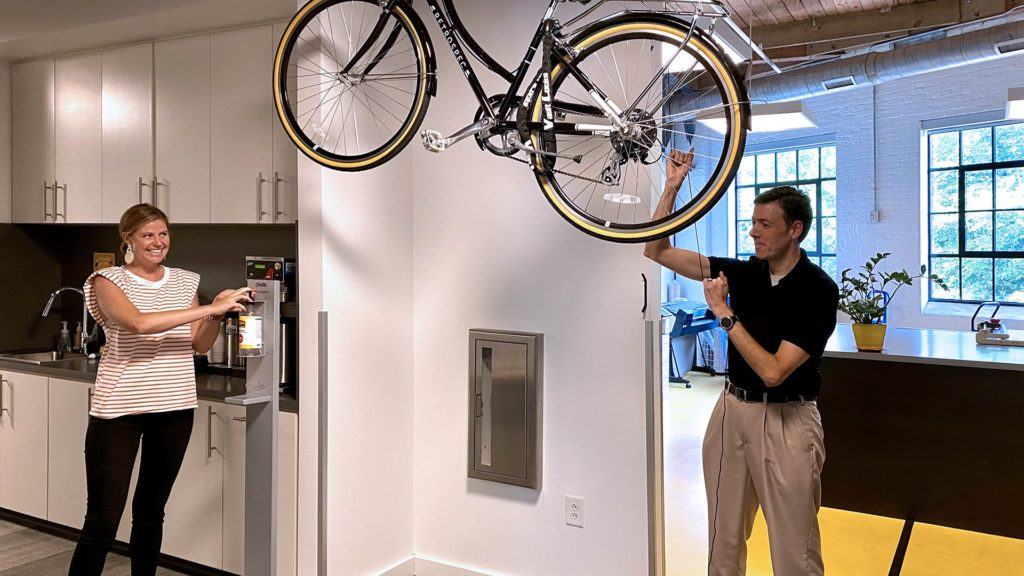 Pictured: Interior designer Lucy Neal uses a hand-sanitizer station while associate architect Tom Lockhart lowers a bike to take out for an exercise break